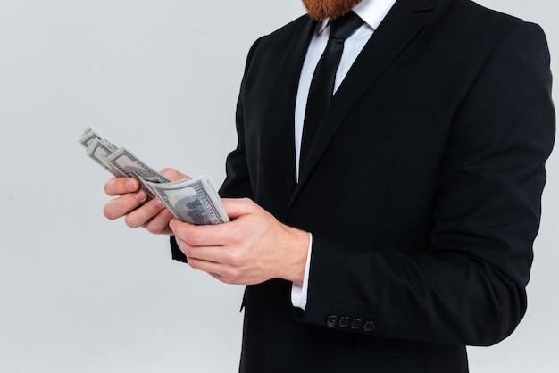 Immagine ritagliata dell'uomo d'affari in abito nero che tiene e racconta i soldi. sfondo grigio isolato