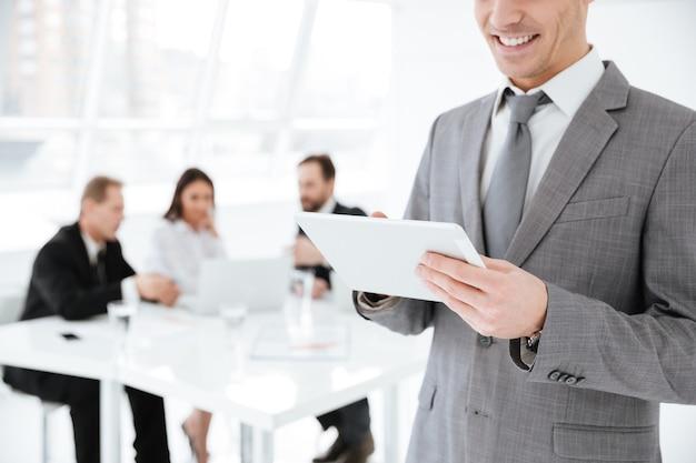 Immagine ritagliata di un uomo d'affari che utilizza un tablet in ufficio con i colleghi al tavolo
