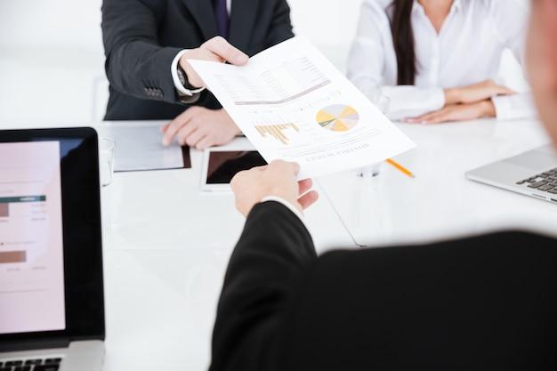 Immagine ritagliata di partner commerciali seduti al tavolo con documenti