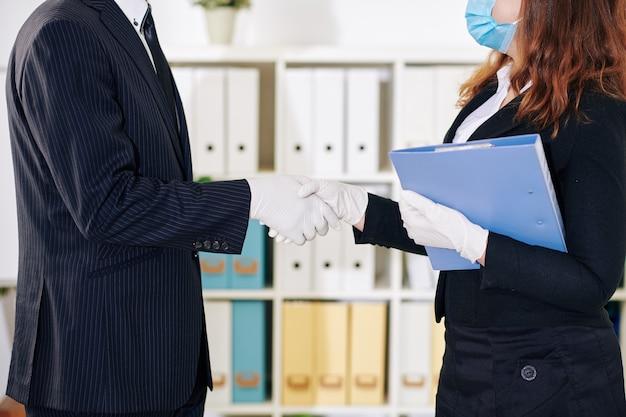Immagine ritagliata di uomini d'affari in guanti di gomma e maschere mediche che agitano le mani prima di incontrarsi