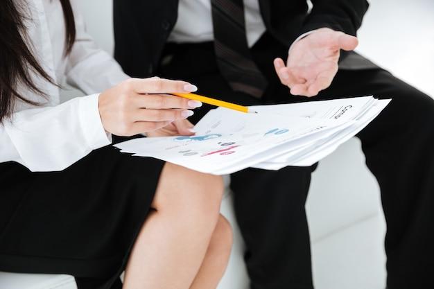 Immagine ritagliata di uomini d'affari seduti sul divano con documenti in ufficio