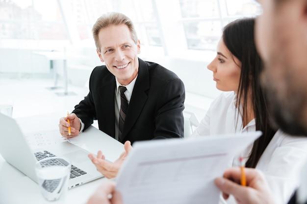 Immagine ritagliata del team aziendale seduto al tavolo durante una conferenza in ufficio