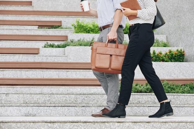 Immagine ritagliata di uomo d'affari e imprenditrice con asporto caffè camminando all'aperto