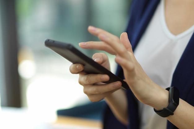 L'immagine ritagliata, il primo piano di una giovane donna d'affari di successo utilizza il testo o il messaggio dello smartphone moderno con il partner cliente online. contatto di lavoro