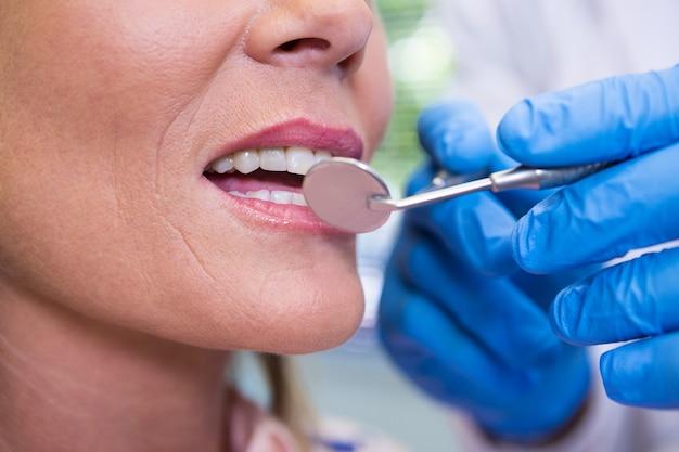 Immagine ritagliata della donna che esamina il dentista