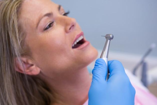 Immagine ritagliata del dentista che tiene attrezzatura medica mentre dà il trattamento al paziente