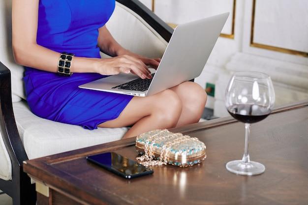 Immagine potata della giovane donna vestita che beve un bicchiere di vino e lavora al computer portatile