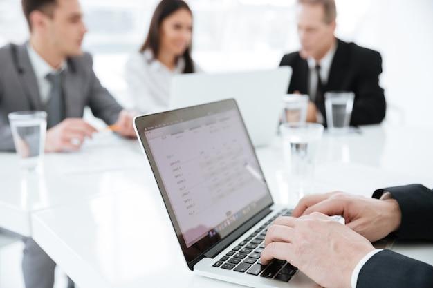 Immagine ritagliata dell'uomo d'affari anziano seduto al tavolo con i partner commerciali e che usa il laptop