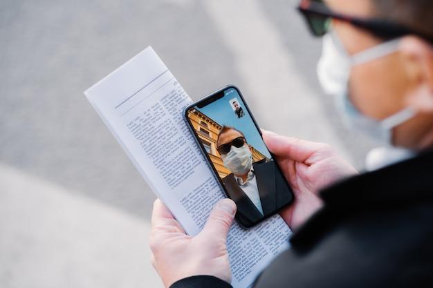 L'immagine ritagliata di un uomo senza volto fa una videochiamata tramite un moderno cellulare, indossa una maschera medica protettiva durante la diffusione del virus, ha solo la comunicazione a distanza per prevenire il coronavirus, tiene il giornale