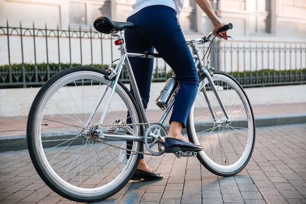 Immagine ritagliata di un motociclista femminile in bicicletta sulla strada