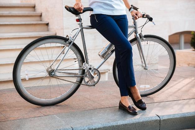 Immagine ritagliata di un motociclista femminile che si siede sulla bicicletta sulla strada
