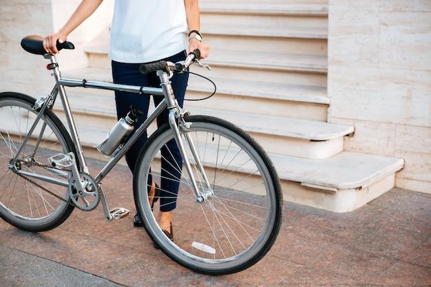 Immagine ritagliata di un motociclista femminile in piedi e tenendo la bicicletta sulla strada