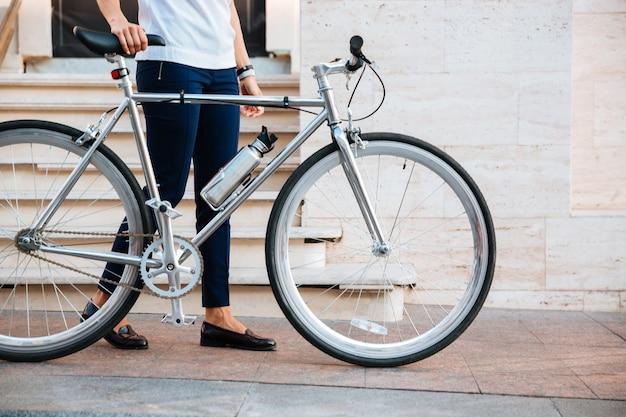 Immagine ritagliata di un motociclista femminile in piedi con la bicicletta sulla strada