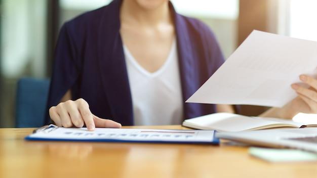 Immagine ritagliata del project manager femminile che cerca documenti finanziari