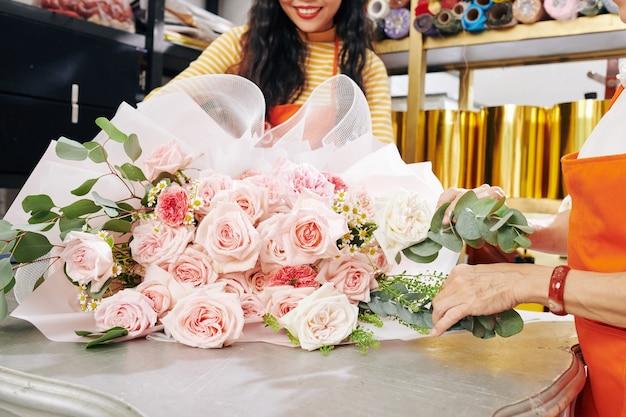 Immagine ritagliata di fioristi che lavorano su un grande bouquet per il cliente con fiori rosa chiaro e bianchi