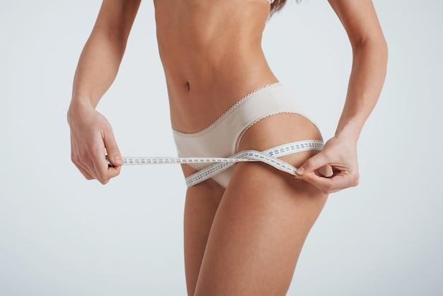 L'immagine ritagliata della ragazza in biancheria intima bianca misura i risultati della forma fisica.