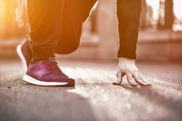 Immagine ritagliata delle mani che legano i lacci delle scarpe su una scarpa da tennis, superficie di corsa