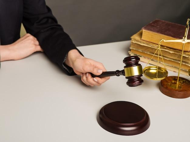 Immagine ritagliata del giudice che dà il verdetto colpendo il martello alla scrivania.