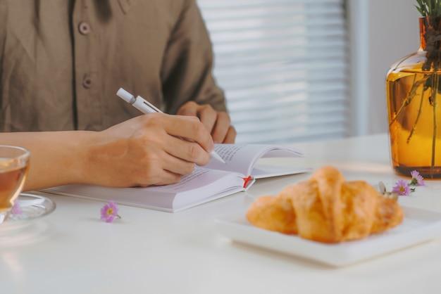 Immagine ritagliata di un uomo seduto al tavolo di legno bianco vintage e tè mentre lavora con il blocco note