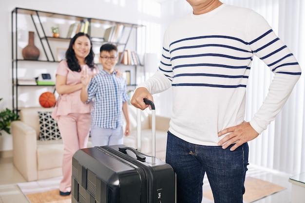 Immagine ritagliata dell'uomo in piedi nel soggiorno con la grande valigia, sua moglie e suo figlio adolescente che fluttuano