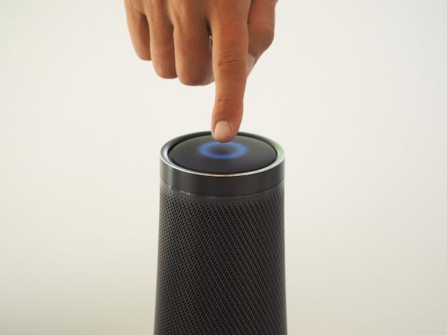 Immagine ritagliata di un uomo che utilizza un altoparlante con assistente vocale di intelligenza artificiale e tecnologia touch.