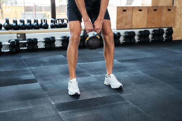 Immagine ritagliata dell'uomo con peso. fare esercizio