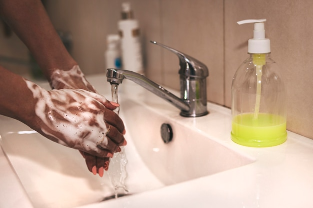 Immagine ritagliata della persona che si lava le mani al lavandino in bagno, lavaggio delle mani di coronavirus per l'igiene delle mani pulite prevenzione della diffusione di covid-19 infezioni virali e batteriche. la donna afroamericana si lava le mani.