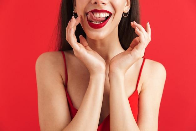 Immagine ritagliata di una giovane donna allegra in abito isolato, tenendosi per mano il viso
