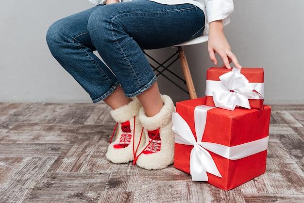 Immagine ritagliata di una donna incinta con regali seduta su una sedia