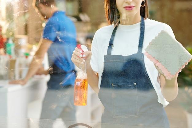 Immagine ritagliata di una bella giovane donna che pulisce finestre o pareti di vetro di un bar o di un negozio di alimentari