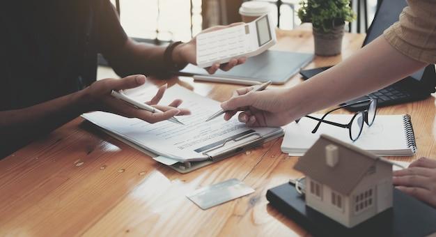 Immagine ritagliata dell'agente immobiliare che aiuta il cliente a firmare la carta del contratto alla scrivania con il modello della casa