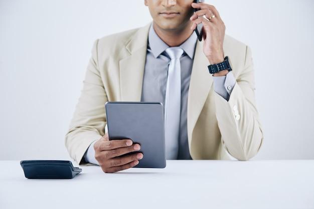 Immagine ritagliata di un giovane uomo d'affari serio che legge la posta elettronica su un tablet e parla al telefono con un partner commerciale o un collega