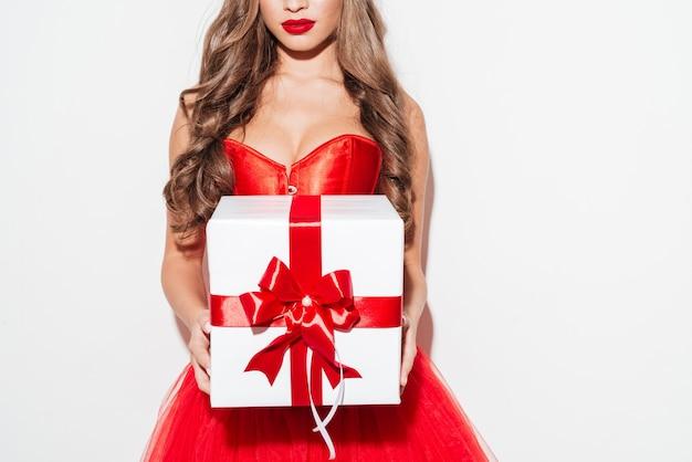 Immagine ritagliata di una donna bruna riccia sexy in abito rosso che dà una grande scatola regalo isolata