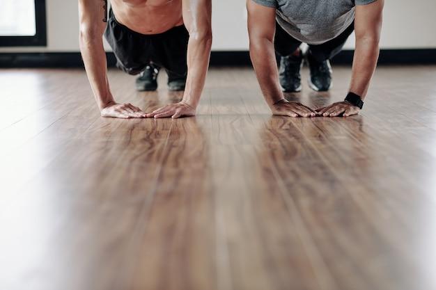 Immagine ritagliata di uno sportivo e il suo personal trainer che fanno flessioni sul pavimento della palestra