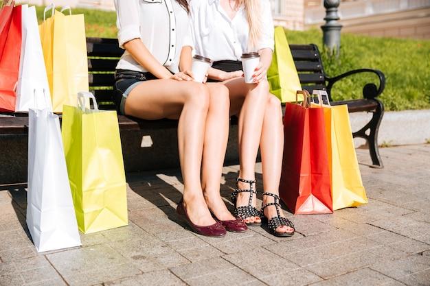 Immagine ritagliata di due donne in appoggio su una panchina insieme a borse della spesa