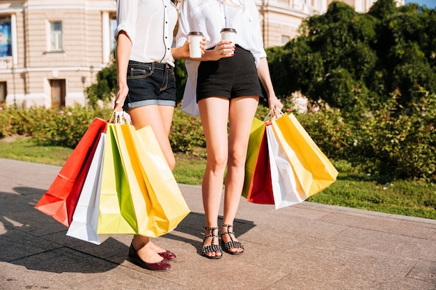Immagine ritagliata di due giovani donne che camminano lungo la strada con borse della spesa e tazze di caffè