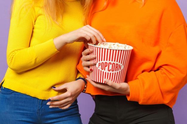 Immagine ritagliata di due ragazze in abiti colorati vivaci che tengono secchio di popcorn isolato su parete blu viola pastello. concetto di stile di vita familiare di persone.