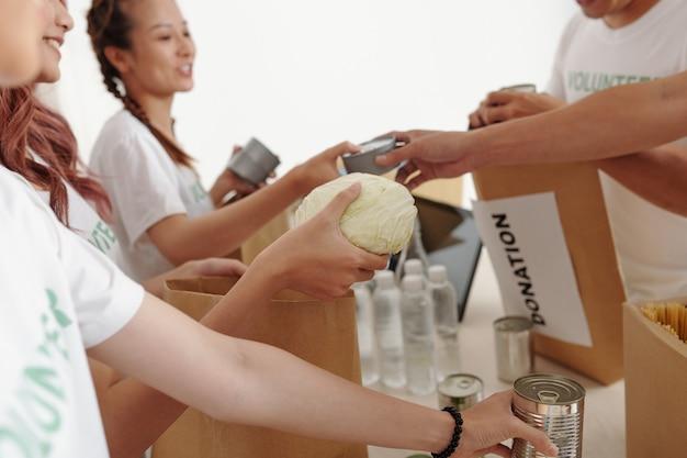 Immagine ritagliata di volontari che confezionano acqua, cibo in scatola e verdure in confezioni di carta per le persone che hanno perso la casa dopo un uragano o un'alluvione