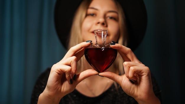 Immagine ritagliata della donna che tiene un vasetto di vetro a forma di cuore di pozione d'amore. bella giovane donna con un cappello da strega