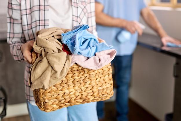 Immagine ritagliata di una donna che tiene in mano un cesto della biancheria pieno di vestiti che vanno a lavare