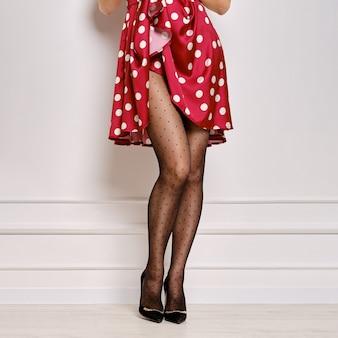 Immagine ritagliata di una donna che solleva un abito punteggiato e mostra collant con motivo a punti