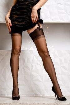 Immagine ritagliata di una donna che solleva un abito corto e mostra calze e reggicalze