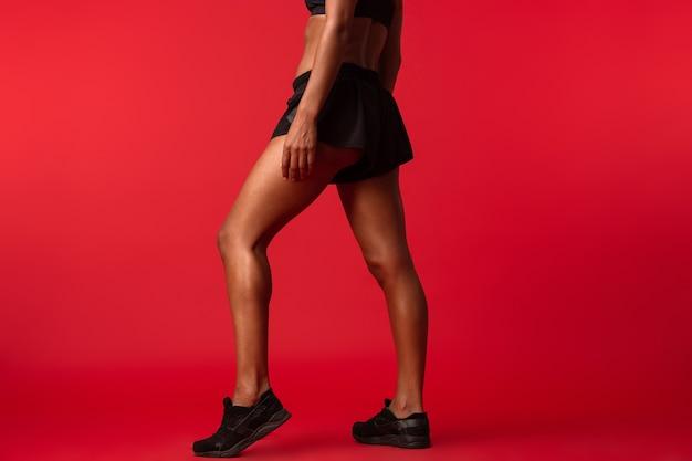 Immagine potata della giovane donna afroamericana in abiti sportivi neri in piedi, isolata sopra la parete rossa