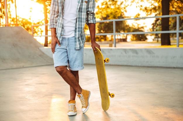 Immagine ritagliata del giovane africano con lo skateboard