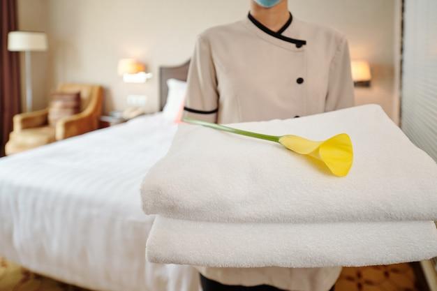 Immagine ritagliata di una giovane cameriera d'albergo in piedi nella suite con una pila di asciugamani freschi e calla lily