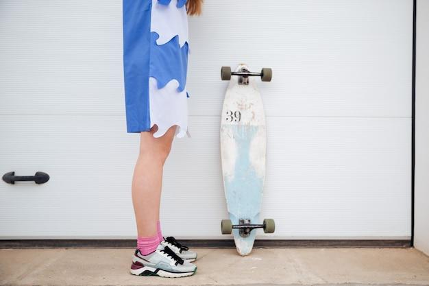 Immagine ritagliata di giovani gambe femminili e skateboard all'aperto sopra bianco