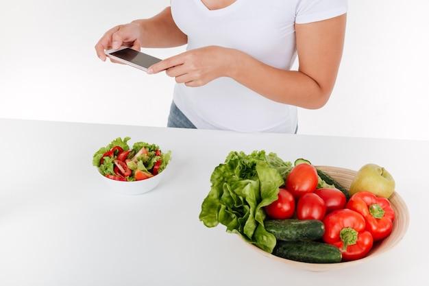 Immagine ritagliata della giovane donna che scatta una foto di insalata di verdure sul suo telefono