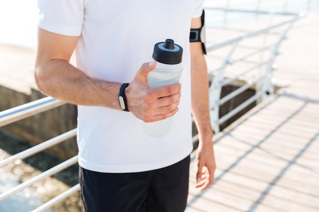 Immagine ritagliata di un giovane sportivo maschio che tiene una bottiglia d'acqua all'aperto