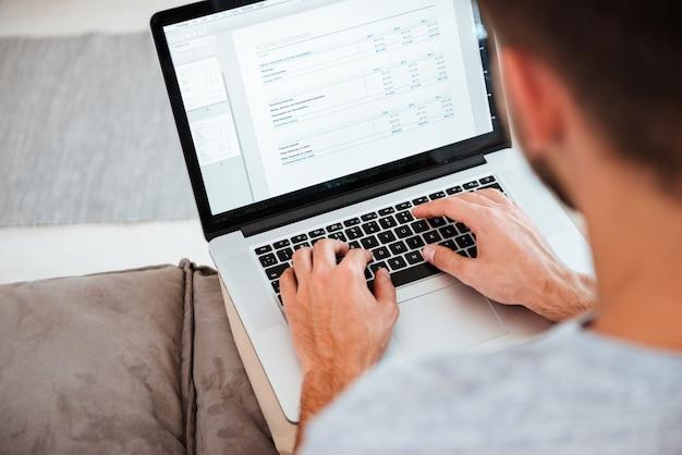 Immagine ritagliata di un giovane uomo che digita sul suo laptop mentre è seduto sul divano. concentrarsi sulle mani che digitano.