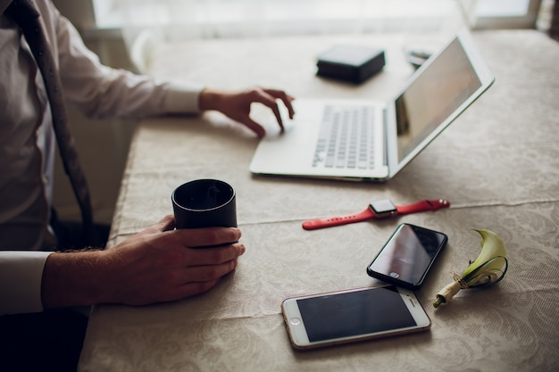 Immagine ritagliata giovane che lavora sul suo computer portatile in caffetteria, vista posteriore di mani di uomo d'affari occupate utilizzando la scrivania del computer portatile, giovane studente maschio digitando sul computer seduto tavolo in legno